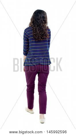 back view of walking curly woman. Long-haired curly girl is looking to the side.