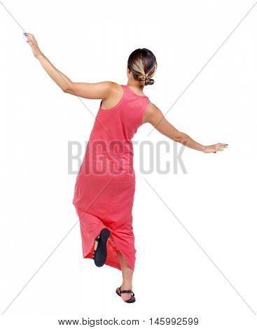Balancing young woman. or dodge falling woman. slender woman in a long red dress balancing on his leg.