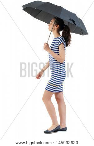 young woman in dress walking under an umbrella. Swarthy girl in a checkered dress comes under the umbrella.