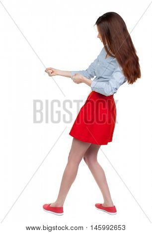 back view of standing girl pulling a rope from the top or cling to something. . Long-haired brunette in red skirt pulling rope side