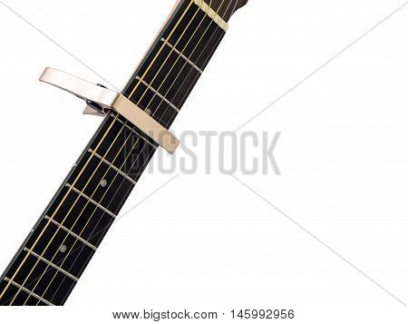Gold capo on guitar fingerboard white background close up