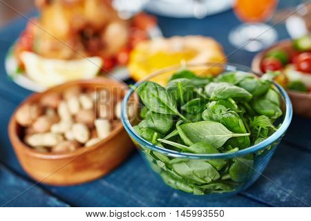 Glass bowl filled with fresh bright green basil leaves standing on rustic wooden table next to smaller bowl of nuts at family feast