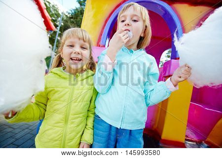 Portrait of two blond girls wearing colorful jackets on playground in amusement park holding big clouds of white cotton candy, eating it and smiling, looking at camera during family weekend