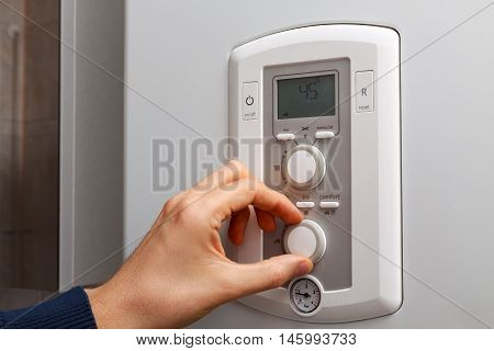 Men hand regulate temperature on 45 degree in control panel of DHW.