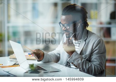 Stylish young African-American businessman working with clients and partners, arranging deals using phone headset and laptop in modern office space behind glass wall