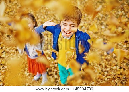 High angle view of two children, boy and younger girl, playing in park, laughing and screaming as they throw fallen golden leaves up around, enjoying warm autumn day
