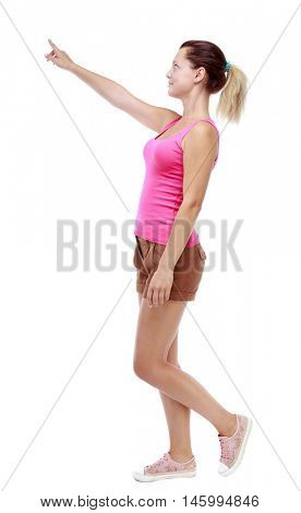 back view of pointing walking woman. going girl pointing. backside view of person. Sport blond in brown shorts walks past the camera pointing to the sky.