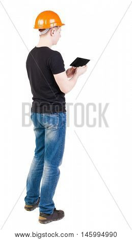 young engineer in a protective helmet with tablet computer in the hands of. girl  watching. Rear view people collection.  backside view of person.  Isolated over white background.