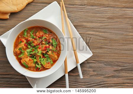 Tasty chicken curry in soup plate and chopsticks on table