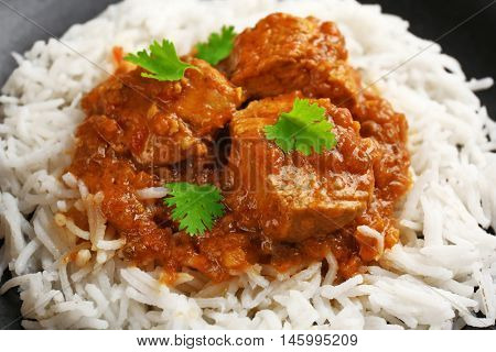 Tasty dinner with chicken curry and rice on plate, closeup