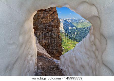 ice tunnel in Sass Pordoi pass on background Fassa Valley