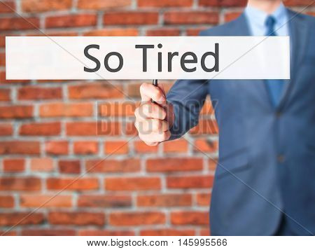 So Tired - Businessman Hand Holding Sign
