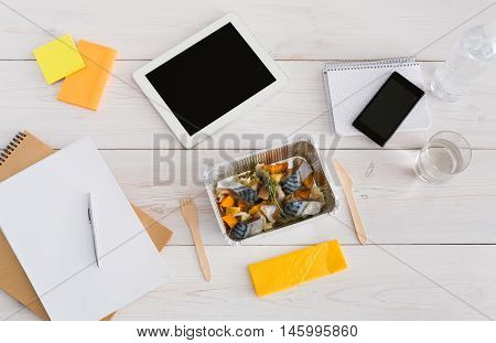 Healthy lunch - foil box with mackerel fish and vegetables with water glass and wooden cutlery on table. Diet food on office table with mobile phone, papers and tablet. Top view, copy space