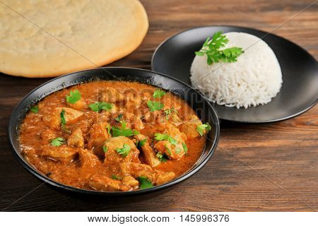 Tasty dinner with chicken curry in bowl on wooden background