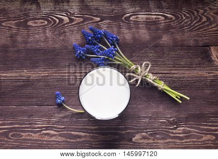 fresh milk in and glass on wooden background. Glass of Milk From Above. Milk in glass and wild flowers bouquet over wooden background close up.