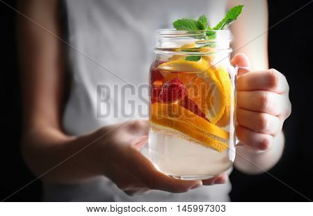 Woman holding refreshing water with fruits