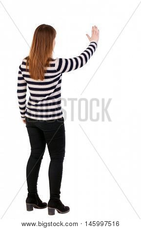 back view of young woman presses down on something. Girl in a striped jacket stands sideways and presses his hand on the button.