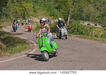 CESENA, ITALY - JUNE 26: biker girl leads a group of bikers riding a vintage italian scooter Vespa on the hills during the rally