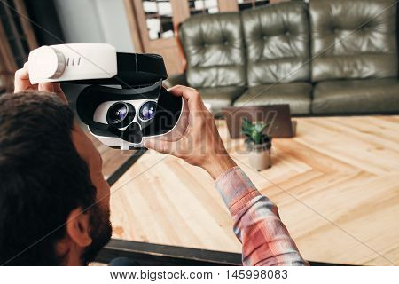 Back view of man wearing virtual reality glasses. Guy preparing to enjoy innovational gadget - vr glasses test. Modern technology, innovation, cyberspace, entertainment concept
