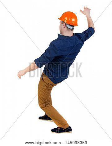 Balancing young man. or dodge the falling man. backside view of person. Isolated over white background. a man in a helmet is strongly leaned back balancing.