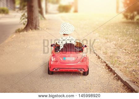 Little Girl Dressed In White Blackheads Shirt And Hat, Driving A Red Toy Car Near The Park. Baby Gir