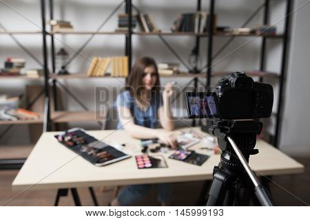 Female vlogger recording video at home. Close-up of camera screen with young blogger face picture. Fashion, beauty, technology concept