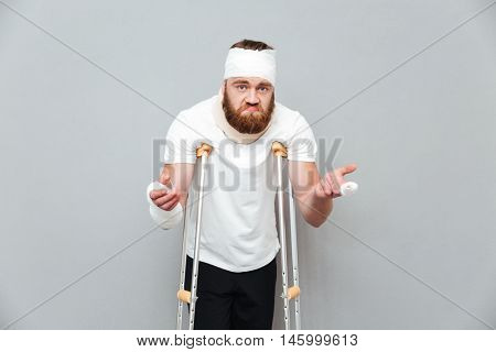 Embarressed puzzled young man standing using crutches over white background