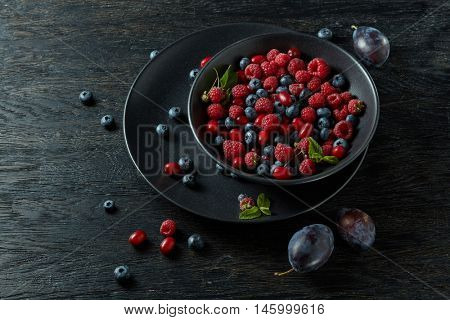 raspberries, blueberries, plum and dogwood. fresh berries on plate
