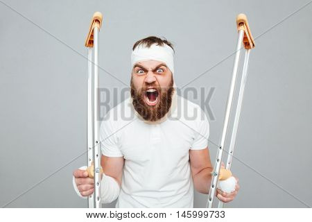 Crazy hysterical young man holding crutches and shouting over white background