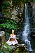 Beautiful young woman meditating in lotus position while doing yoga in the nature near waterfall