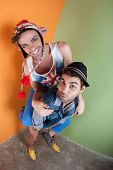 picture of sock-monkey  - Two handsome men playing piggyback in front of green and orange walls - JPG