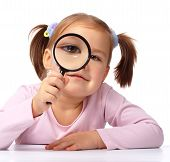 pic of cute little girl  - Curious little girl is looking through magnifying glass isolated over white - JPG