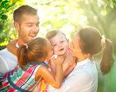 Happy joyful young family with children. Father, mother and little kids having fun outdoors in orcha poster