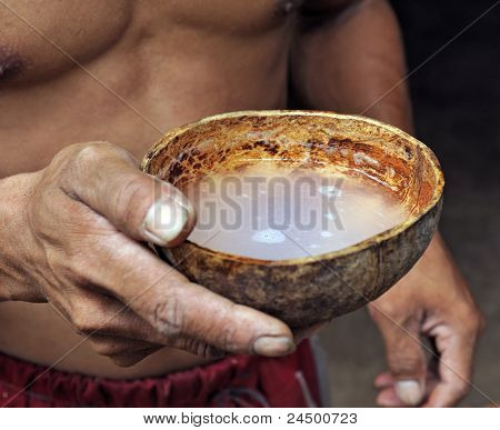 Asian man drinking from coconut shell