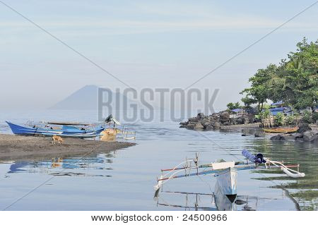 Asian outrigger boats, harbor and volcano