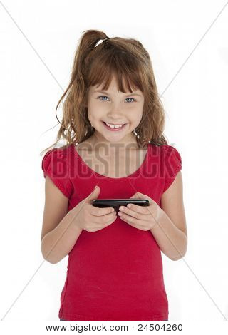Seven year old girl holding cell phone, smiling at camera, on white background.