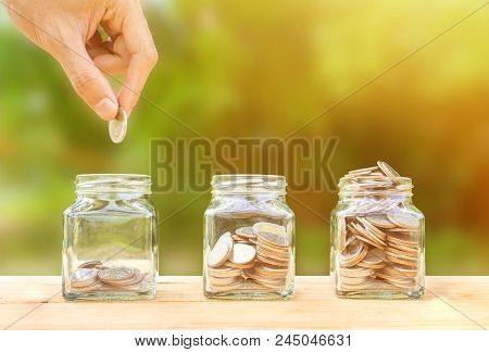 poster of Saving And Invest Money Concept. Conceptual Hand Putting Coins Into Bottle On Nature Background. Bus