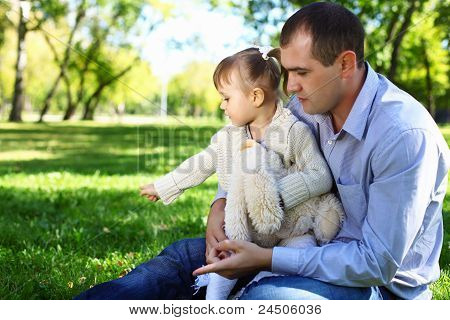 Young family with little daughter in summer park