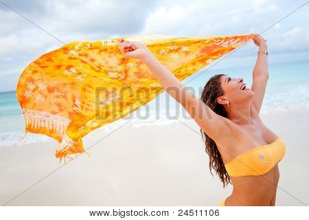 Woman feeling the wind while holding a sarong at the beach - freedom concepts