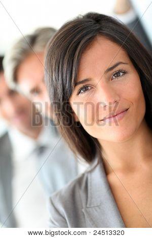 Hermosa vendedora permanente con el grupo de empresarios