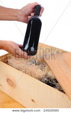 Man holding a single wine bottle over wooden crate filled with bottles and packing material. Vertical isolated over white.