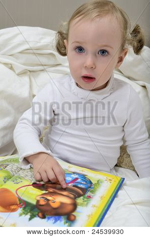 Little Girl Sitting On The Bed And Reading A Book