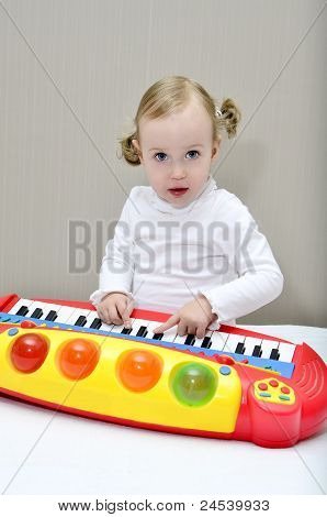 Little Girl Sitting On The Bed And Plays On A Children's Keyboard