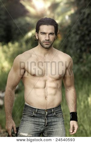Portrait of a hunky male fitness model shirtless in beautiful outdoor natural setting