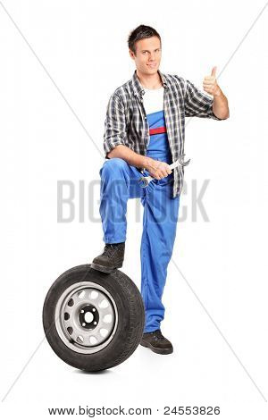 A smiling mechanic giving a thumb up with a spare tire and wrench isolated on white background