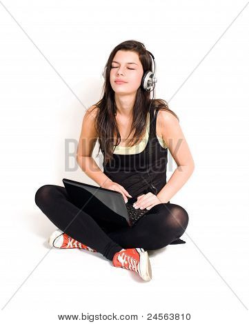 Gorgeous Young Brunette Listening To Music Using Laptop.