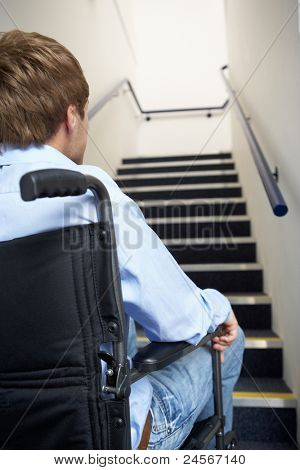 Man in wheelchair at foot of stairs