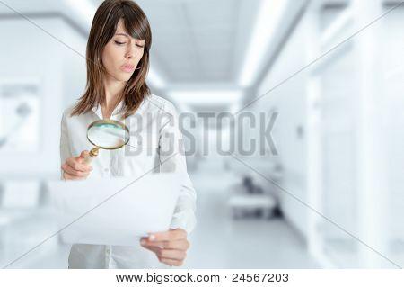 Mujer joven en el hospital de examinar un documento con una lupa