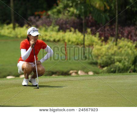KUALA LUMPUR, MALAYSIA - OCTOBER 16: Malaysian amateur Kelly Tan prepares for her putt on day 4 of the Sime Darby LPGA Malaysia 2011 golf tournament on Oct 16, 2011 in Kuala Lumpur, Malaysia.