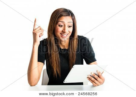 Attractive young asian indian teenage woman, working with a portable tablet computer looking angry and frustrated